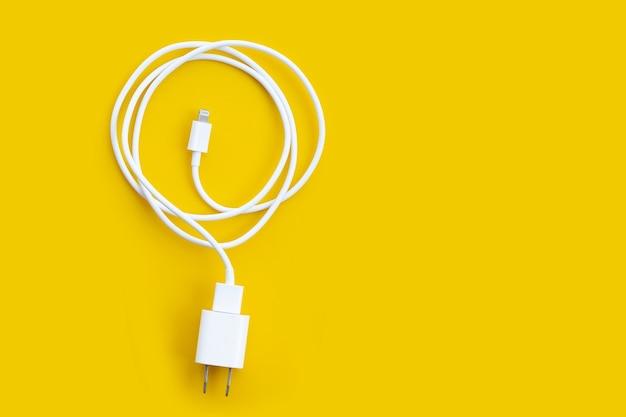 노란색 바탕에 휴대 전화 충전기입니다.