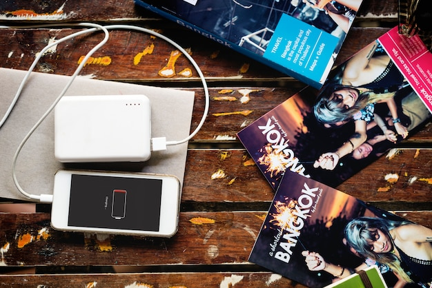 Mobile phone chargin with power bank lying with bangkok thailand travel guide book brochure