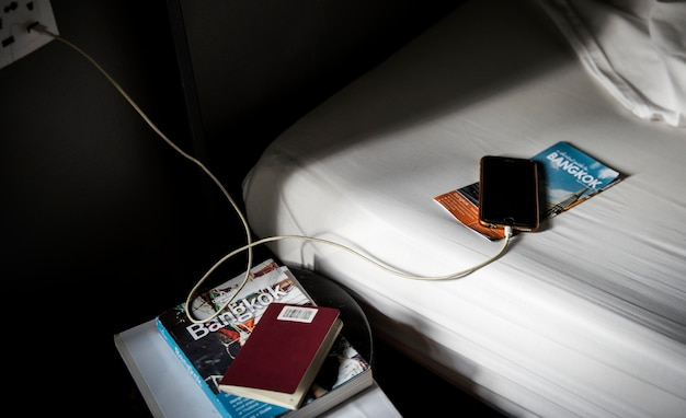 A mobile phone charging lying on the bed with a bangkok, thailand travel guide book and brochure