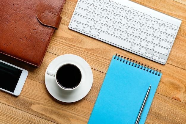 携帯電話、コンピューターのキーボード、メモ用のメモ帳、コーヒー・マグと花、木製テーブルの上。ビジネスマンや職場のマネージャーのアイテム。