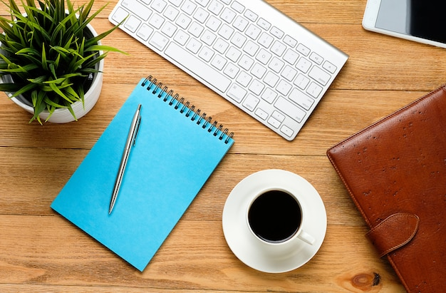 A mobile phone, a computer keyboard, a pen and notepad for notes, a coffee mug and a flower on a wooden table. subjects of work of a businessman or manager in the workplace.