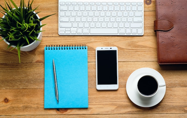 A mobile phone, a computer keyboard, a pen and notepad for notes, a coffee mug and a flower on a wooden table.