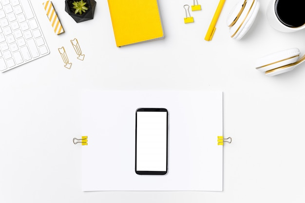 Mobile phone on designer workplace mockup top view