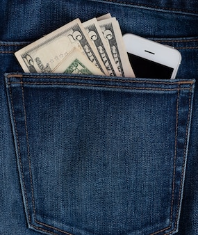 Mobile phone and dollar bills in jeans pocket