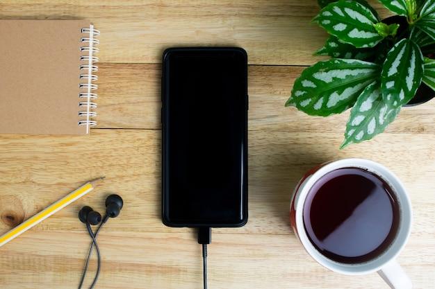 Мобильный телефон наушники записной книжки карандаш горшок и кубок вид сверху на деревянный стол