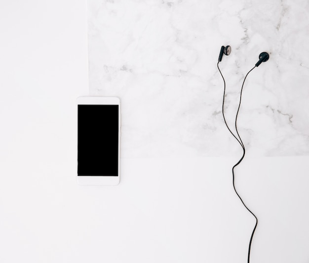 Mobile phone and earphone on white textured background