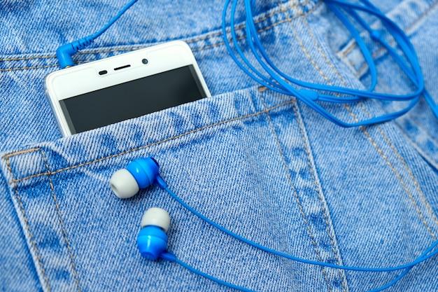 Mobile phone, earphones in poket blue classic jeans