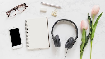 Mobile phone; eyeglasses; notebook; stationery; headphone and pink tulips on marble backdrop