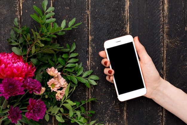 Mobile phone in female hand and a bouquet of flowers on a black wood