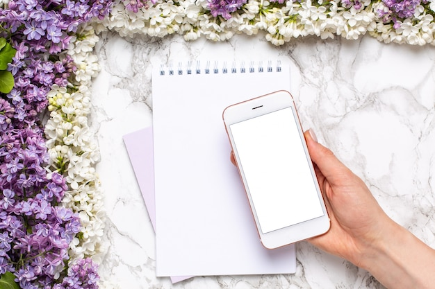 Mobile phone in hand, notebook and frame of white and lilac flowers on marble table in flat lay style.