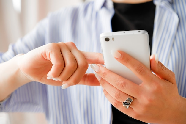 Mobile phone in the hands of a stylish fashion girl freelancer. a young woman in a black t-shirt and striped shirt, with a beautiful manicure holding the phone