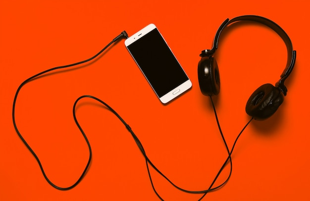 Mobile phone and headphones on bright