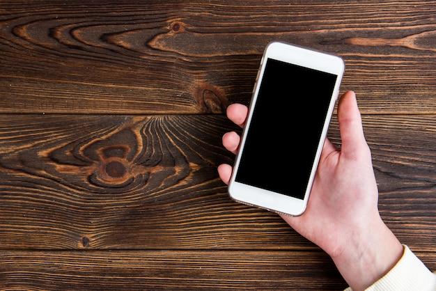 木の板に手に携帯電話