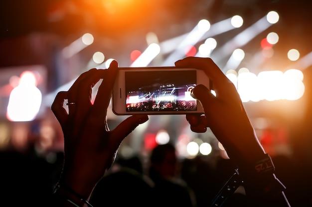 음악 쇼에서 손에 휴대 전화입니다. 스마트 폰 개념을 사용합니다.