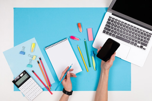 Мобильный телефон в руках, ноутбук, канцтовары, изолированные на белом и синем