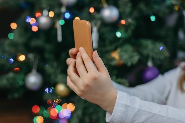 Мобильный телефон в руках девушки на фоне новогодней елки. интернет-поздравления с новым годом. покупки в интернет магазине.