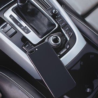 Mobile phone in the interior of a modern car