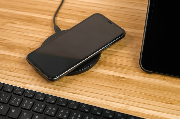 Mobile phone is charging on wireless charging next to the tablet and keyboard on the wooden table. modern device for home office, freelance or distance study. copy space for advertising.