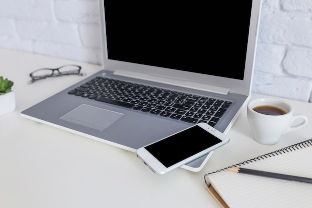 Mobile phone on the laptop with coffee cup on white desk