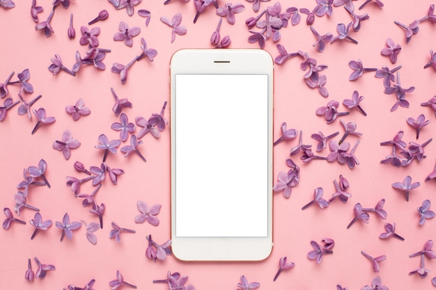 Mobile phone lilac flowers on pink pastel table in flat lay style. woman working desk. fashion color