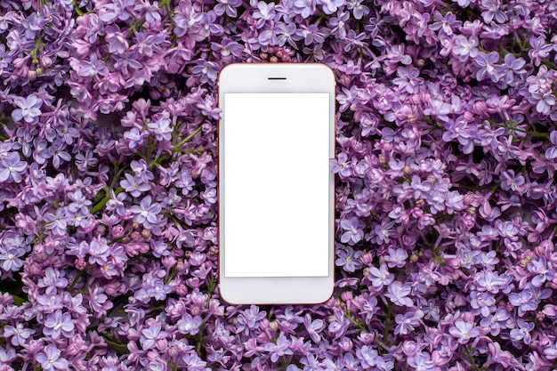 Mobile phone and lilac flowers. summer color and holiday concept.