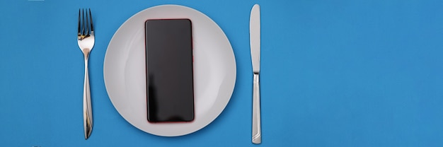 Mobile phone lying in white plate near fork and knife
