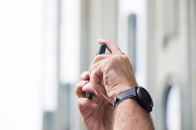 Mobile phone and mans hands with watch
