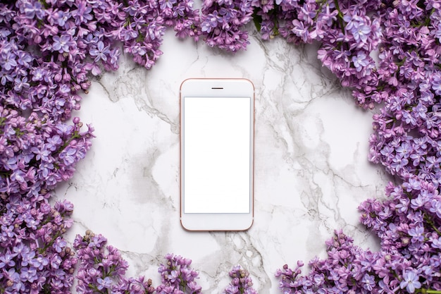 Mobile phone on marble table and lilac flowers