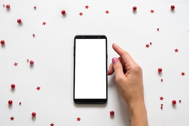 Mobile phone in the middle of christmas composition in white and red decorations