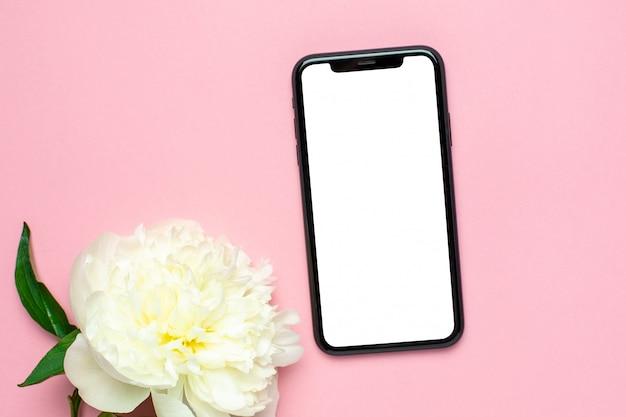 휴대 전화를 모의 핑크 파스텔 테이블에 모란 꽃. 여자 책상. 여름 색 프리미엄 사진