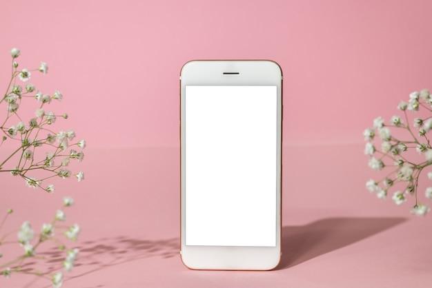 携帯電話のモックアップとピンクの背景に白い花。春のパステルカラー、ハードシャドウの側面図