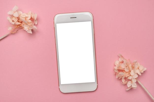 携帯電話のモックアップとピンクの背景に白い花。春のパステルカラーの上面図