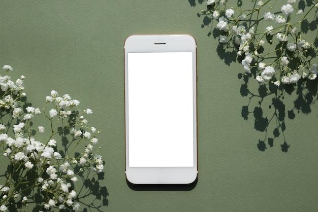 白い小さな花の上面図で飾られたパステルグリーンの背景に携帯電話のモックアップ