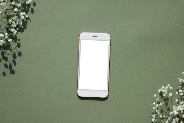 白い小さな花で飾られたパステルグリーンの背景に携帯電話のモックアップ