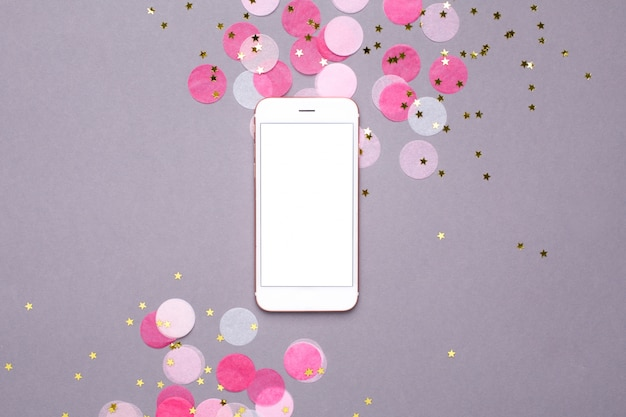 Mobile phone mock up and pink confetti with gold stars on gray