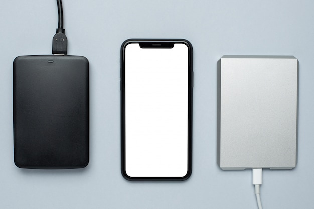 Mobile phone mock up and removable hard drives on gray