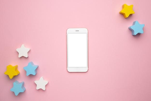 ピンクの背景の上面図に、携帯電話のモックアップ画面と運動技能の発達のための子供の発達玩具、三日月形の木製スターバランサー