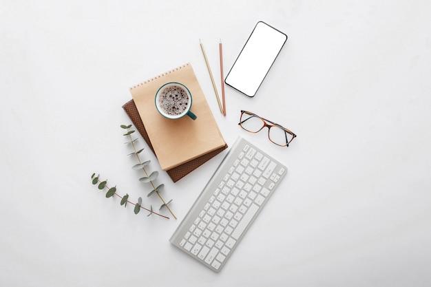 현대적인 작업 공간 책상에 있는 휴대폰 모형. 빈 전화 화면은 컴퓨터 키보드와 사무용품으로 복사 공간을 조롱합니다. 플랫 레이.