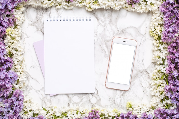 Mobile phone, notebook and frame of white and lilac flowers on marble table in flat lay style.