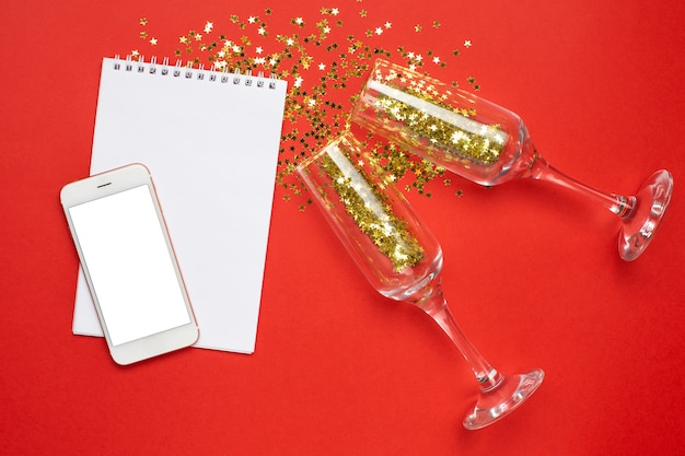 Mobile phone, notepad and champagne glasses with golden stars confetti, christmas and new year concept