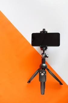 カラーペーパーの背景のための明確なディスプレイを備えた三脚上の携帯電話。