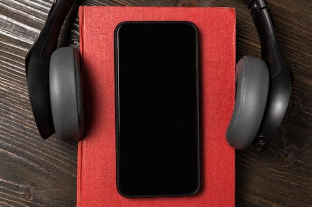 Мобильный телефон на книге с наушниками. понятие аудиокниг. вид сверху крупным планом