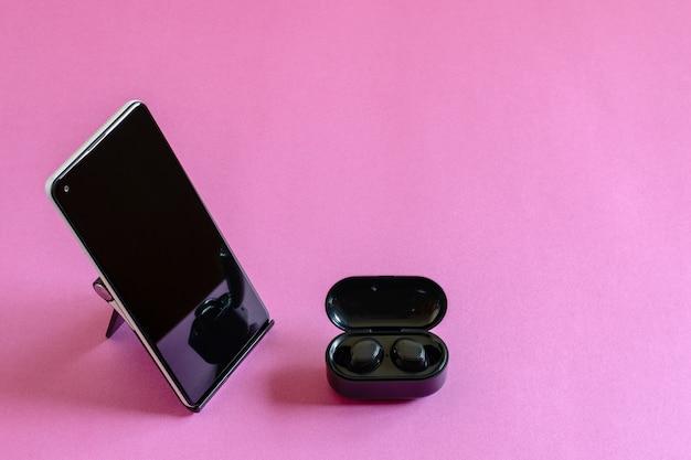 Мобильный телефон на подставке для телефона и беспроводные наушники крупным планом, квартира лежала на розовом фоне. концепция современной технологии.