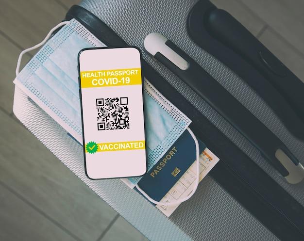Мобильный телефон на чемодане и паспорт здоровья свидетельства о вакцинации на экране