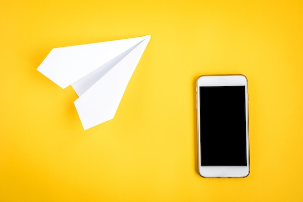 Mobile phone and paper airplane on yellow