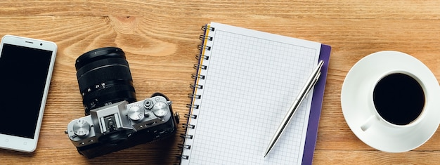 Mobile phone, pen, notepad, mug of coffee and a camera on a wooden table