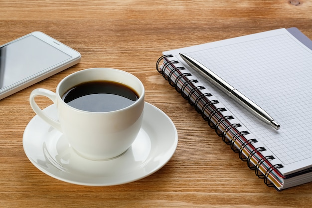 Mobile phone, pen and notepad for notes, coffee mug, on wooden table. subjects of work of a businessman or manager in the workplace.
