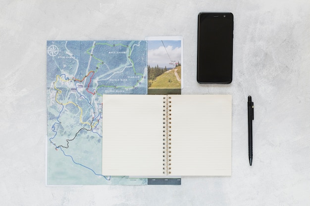 Mobile phone, pen and spiral notebook on map over the background