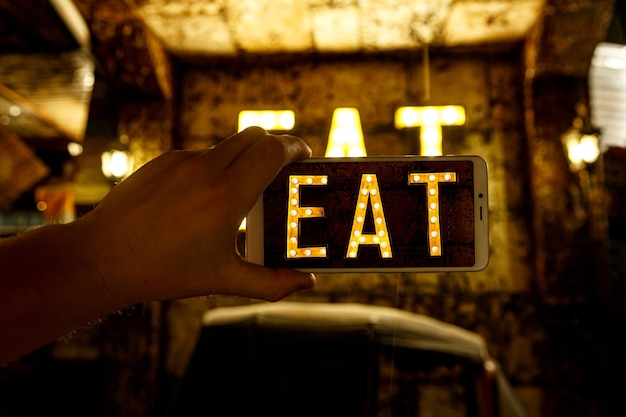 Mobile phone photography. image of word eat written by light bulbs.