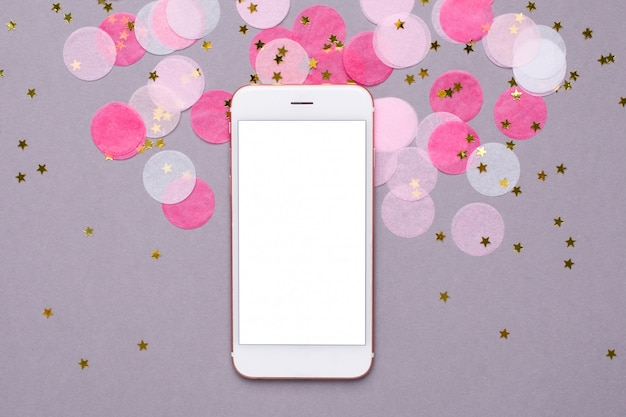 Mobile phone and pink confetti with gold stars on gray